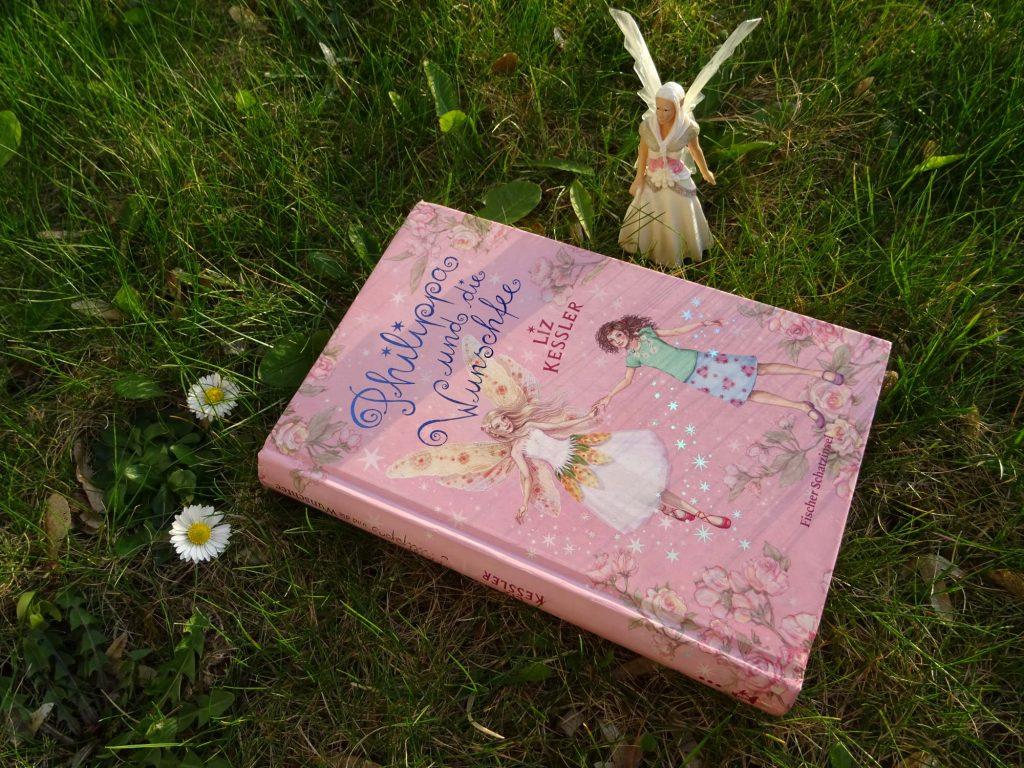 """Buch: """"Philippa und die Wunschfee"""" von Liz Kessler liegt auf der Wiese mit Gänseblümchen. Daneben steht eine Feenfigur."""