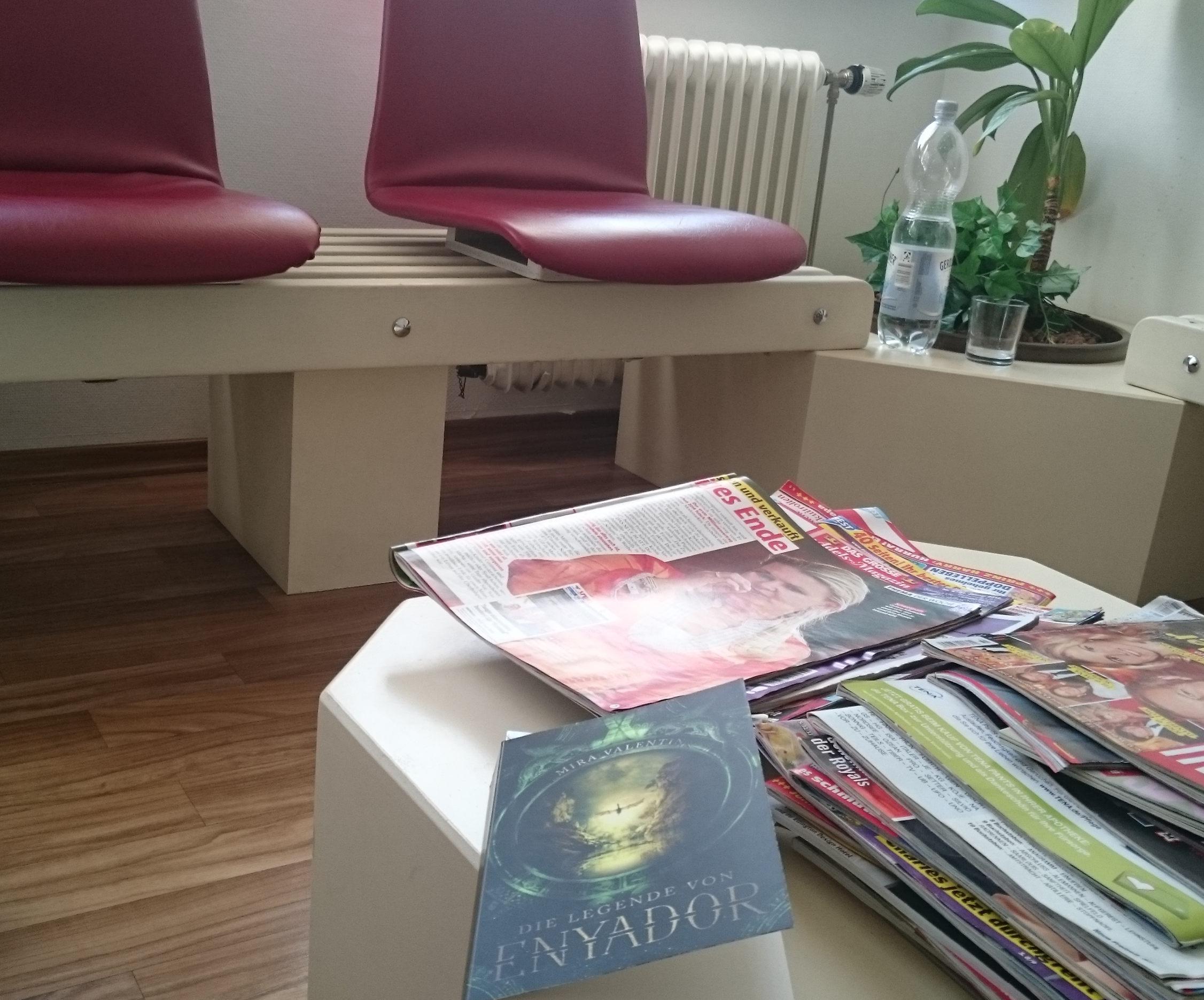 Enyador von Mira Valentin - als Leseplätzchen im Wartezimmer aufgenommen. Das Buch liegt auf dem Tisch mit den Zeitschriften, im Hintergrund sieht man Stühle, eine Pflanze und eine Flasche Wasser