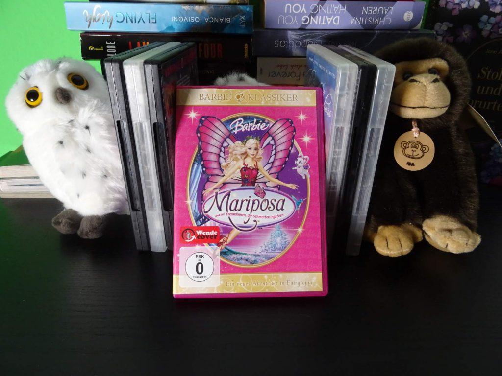 Barbie Mariposa neben anderen DVDs zwischen einer Eule und einem Affen