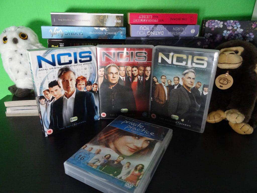 DVDs von NCIS und Pricate Practice zwischen einer Eule und einem Affen. Im Hintergrund Bücherstapel.