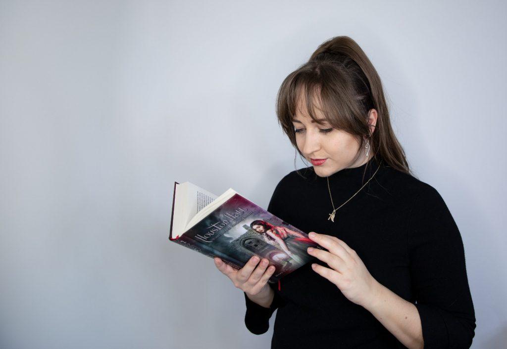 Mary Cronos hält ihr Buch Houston Hall geöffnet in der Hand und liest