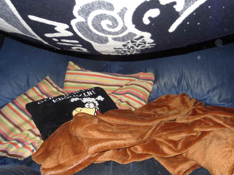 """Sofahelden, Kissen und Decke auf dem Sofa und """"eine Decke droht auf den Kopf zu fallen"""""""