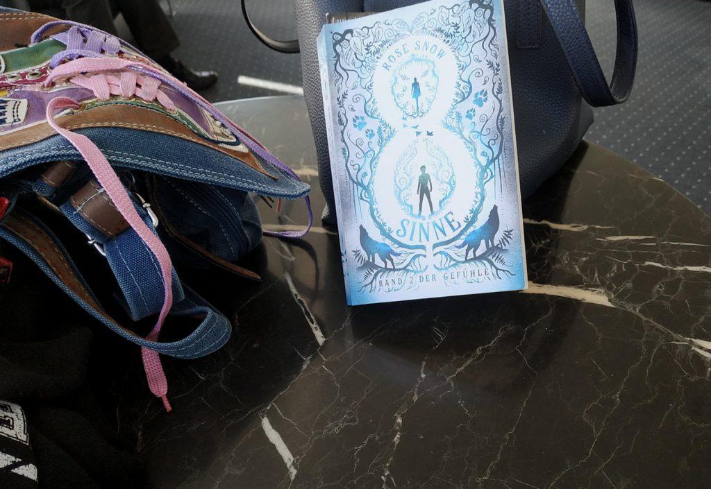 8 Sinne das erste Buch der Gefühle auf einem kleinen Tisch in einem Wartezimmer, gelehnt an eine Handtasche, daneben eine weietre Handtasche.