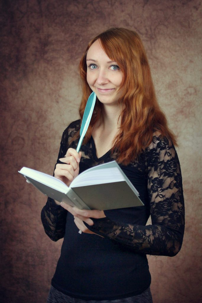April Wynter Porträt mit offenem Buch in der einen und Schreibfederin der anderen Hand.
