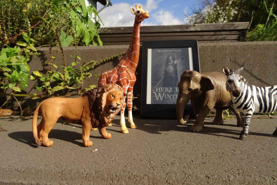 """eBook """"Herz des Winters"""" von Madeleine Puljic und Schleich Figuren: Löwe, Giraffe, Elefant und Zebra als Symbol für die Toolsafari"""
