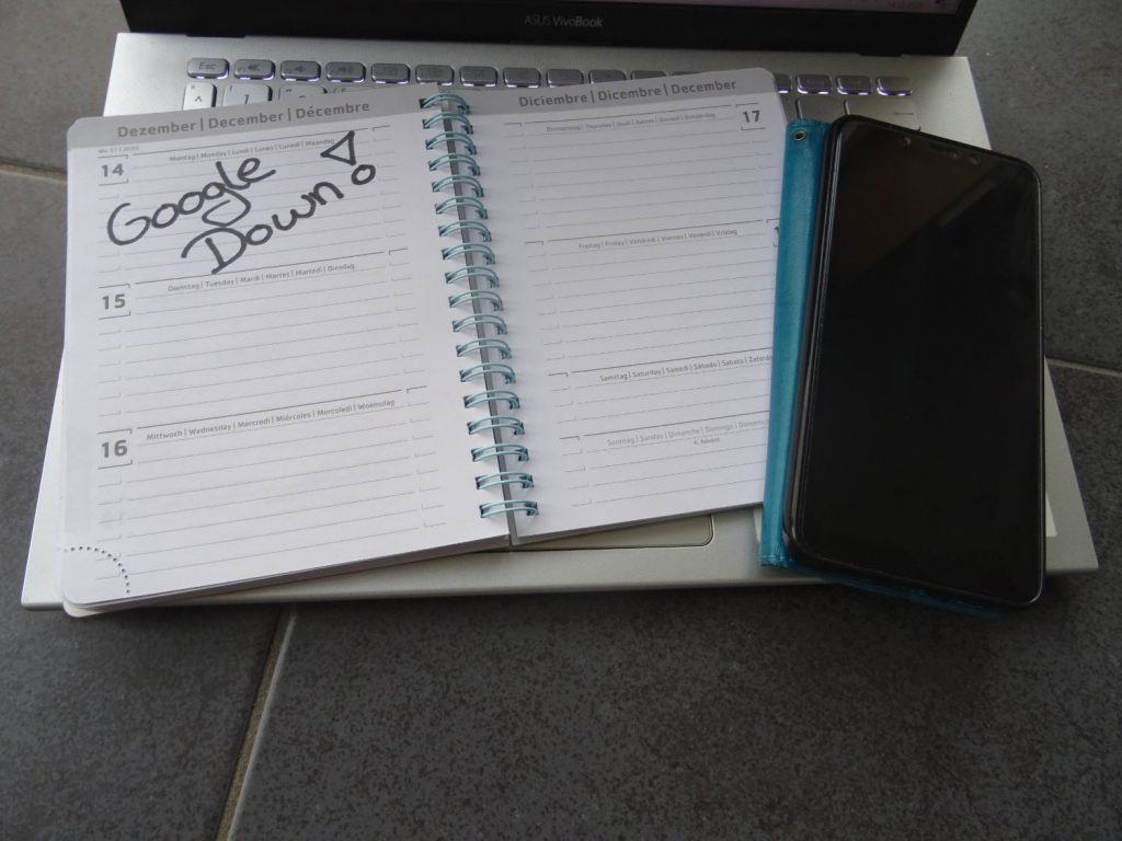 Kalender aufgeschlagen für den 14.12. Eintrag: Google down! Der Kalender liegt auf einem Notebook, daneben das Smartphone mit dunklem Disply