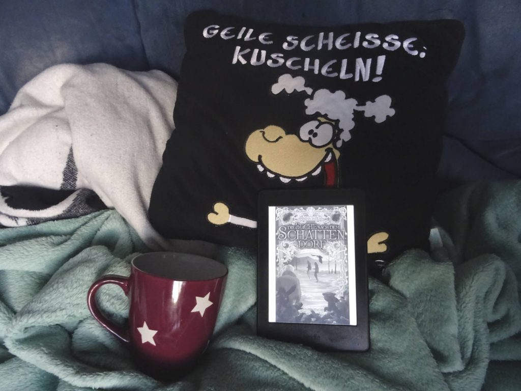 """Kuscheldecken und Kuschelkissen mit Sternetasse und E-Reader mit """"Suche nach dem Schattendorf"""" von Annina Safran"""