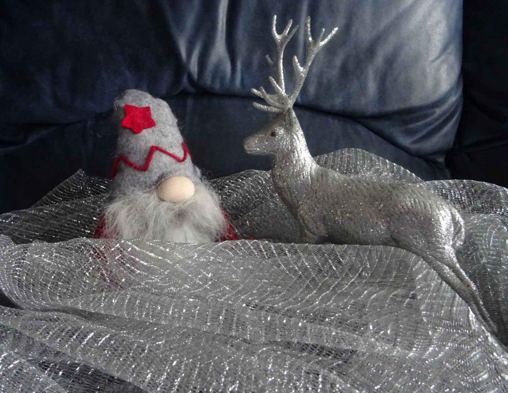 silberner Glitzerelch und ein Weihnachtswichtel stehen sich gegenüber