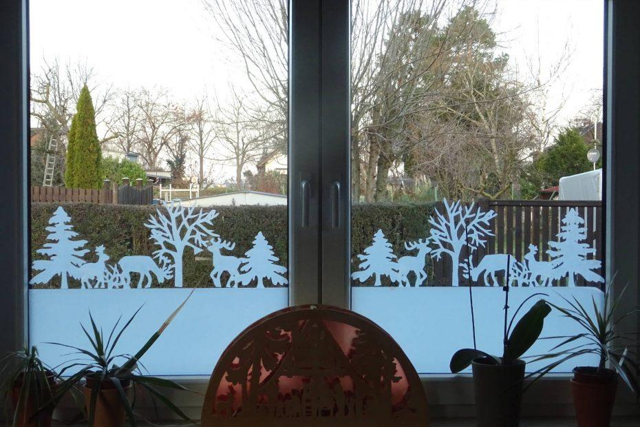 Ein Fensterbild aus weißer Fensterfolie, Bäume und Rentiere.