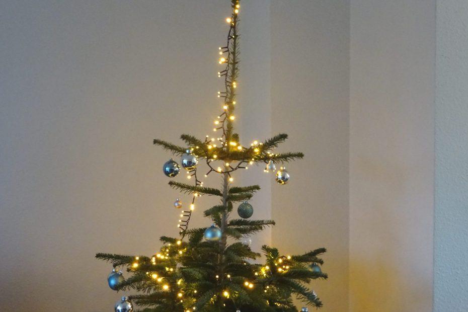 Spitze des geschmückten Weihnachtsbaumes mit Lichterkette und Kugeln
