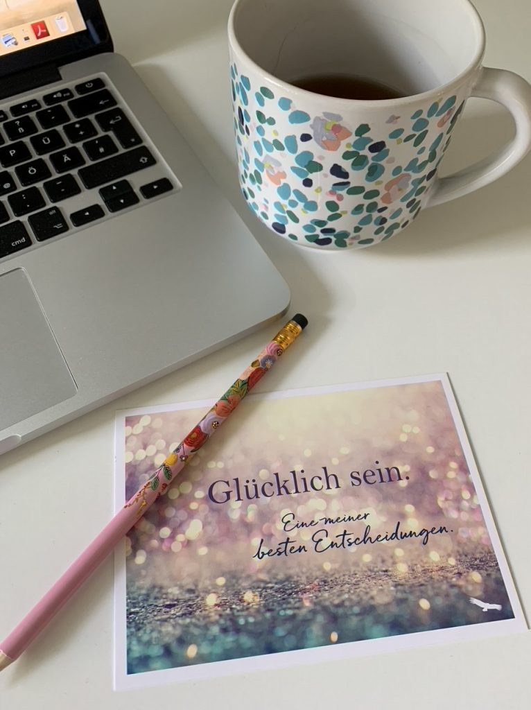 """Auszug des Schreibtisches von Katja von Eysmondt, mit Notebook, Teetasse, Stift und Postkarte mit dem Sprich """"Glücklich sein. Eine meiner besten Entscheidungen."""""""