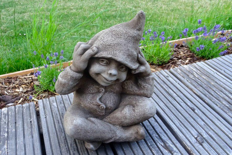 Steinfigur Wichtel mit Zipfelmütze auf der Holzterrasse, im Hintergrund Lavendel und Wiese.