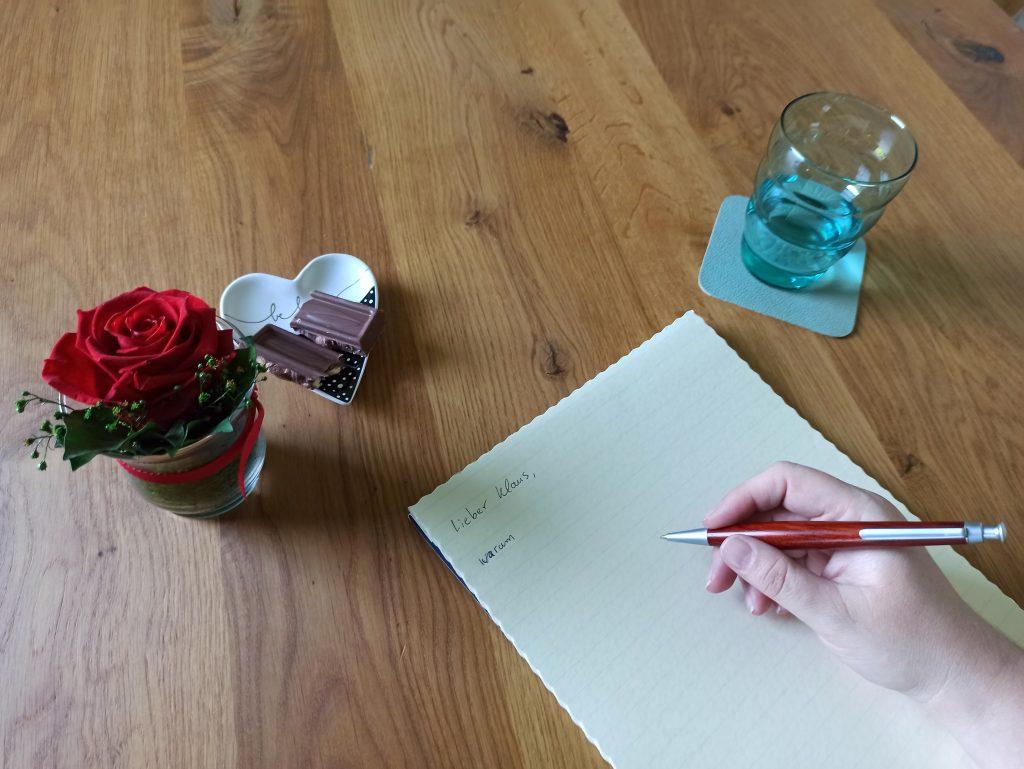ein angefangener Brief mit schreibender Hand, daneben eine Rose, Schokolade und ein Glas Wasser