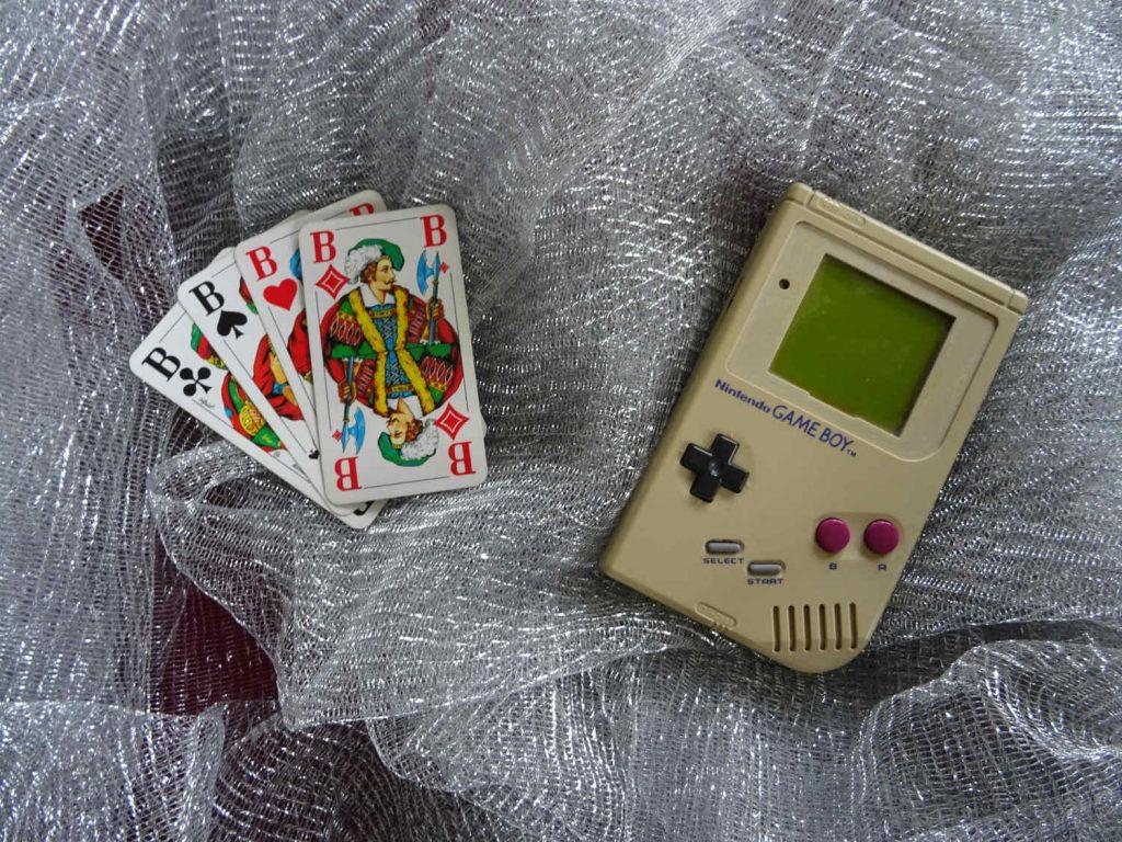 4 Buben aus einem Skatspiel und ein alter Gameboy