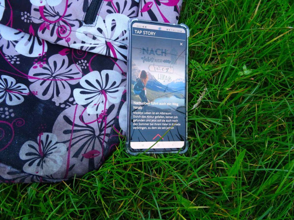 Nach oben führt auch ein Weg hinab ~ April Wynter Smartphone mit geöffnetem Buch in der App Livley Story liegt halb auf einem Rucksack, halb auf der Wiese
