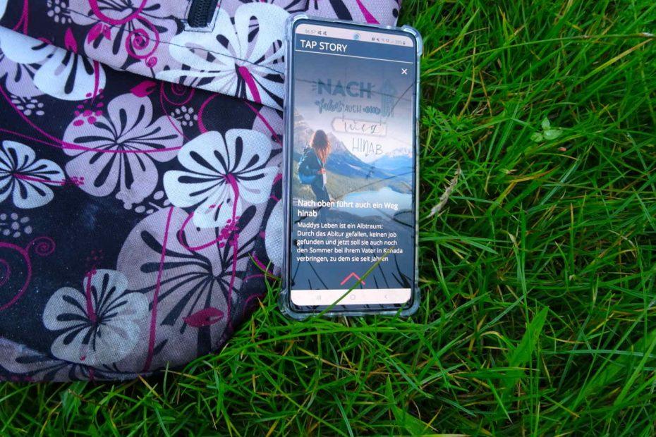 Nach oben führt auch ein Weg hinab ~ April Wynter Smartphone mit geööfnetem Buch in der App Livley Story liegt halb auf einem Rucksack, halb auf der Wiese