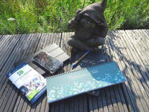 Steinmännchen auf der Terrasse mit Tablet & Smartphone, Programmheft der Digitalen Woche Rhein-Erft, einem Notizbuch, Kalender für 2022 und einem Kugelschreiben