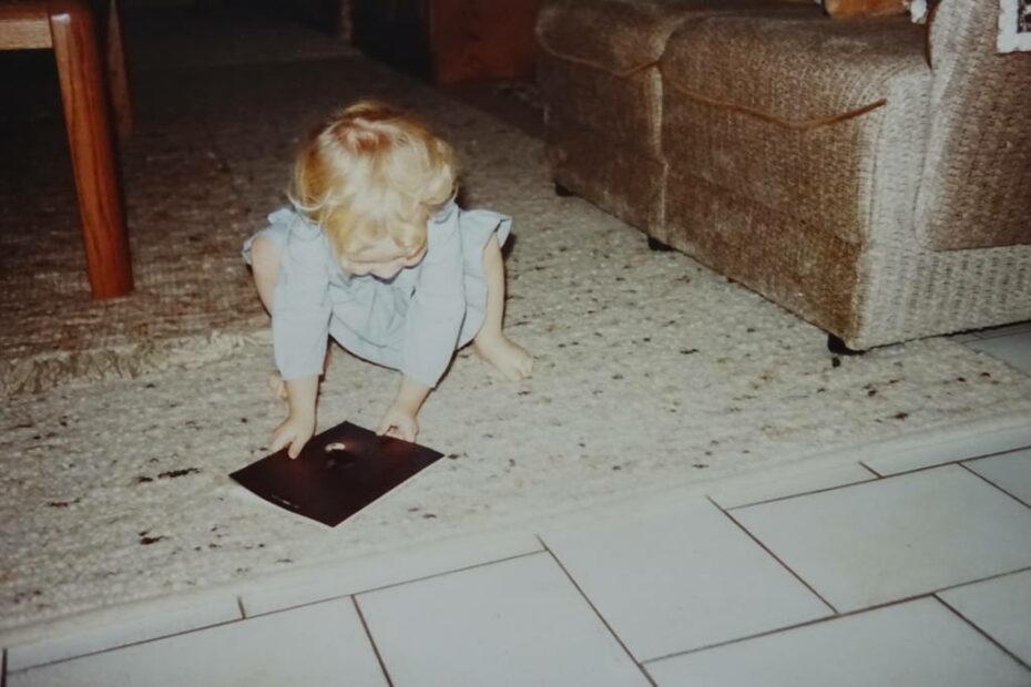 Klein-Stephanie hockt mit einem Buch auf dem Boden